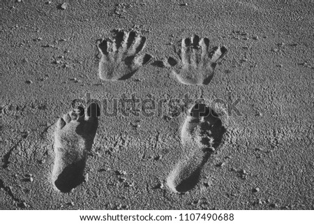 Palms, fingers, feet, toes marks. Vacation, travel, wanderlust. Human imprints prints tracks on sandy surface Handprints and footprints on sand #1107490688