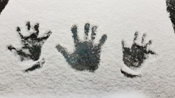 Palms of human hands imprints into white snow covered dark glass surface. Kid's and adult's handprints closeup. Concept of winter fun and cold weather activity. Snowy texture. Winter background.