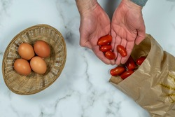 Palms of male hands hold small red cherry tomatoes surrounded by a paper bag and a basket of eggs, to represent the protection of the planet with eco-sustainable materials and zero-kilometer products