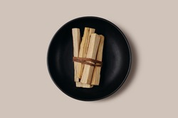 Palo Santo sticks tied in a bunch on a black plate. Top view. Organic holy tree incense from Latin America. Color photo close-up of natural frankincense.