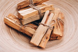 Palo Santo tree sticks in wooden bowl - holy incense tree from Latin America. Meditation, mental health and personal fulfilment concept, selective focus