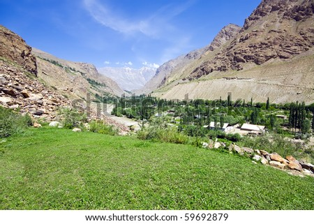 Pamir mountain green meadow and rapid river under blue sky