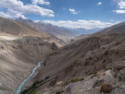 Pamir river gorge in the high-altitude desert between Afghanistan and Tajikistan in the Wakhan Corridor with Hindu Kuch snow-capped mountain range in the background, Gorno-Badakshan