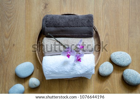 pampering towels and zen stones on round wooden background for concept of pure sensuality, clean softness or chic bodycare, top view still life #1076644196