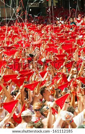 PAMPLONA, SPAIN - JULY 6: Cheering people with red shawl in square in July 6, 2013 in Pamplona, Spain. Opening of San Fermin Festival