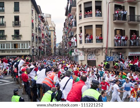 PAMPLONA, SPAIN -JULY 9: Unidentified men run from the bulls in the street Estafeta during the San Fermin festival in Pamplona, Spain on July 9, 2012.