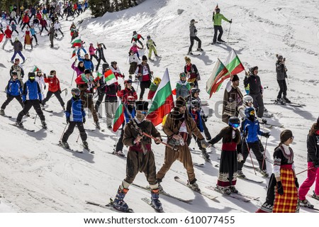 PAMPOROVO, BULGARIA - MARCH 03, 2017 - Skiing with Bulgarian flags at Pamporovo, Bulgaria. People dressed with traditional bulgarian clothes skiing with the national flag. #610077455