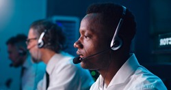 Pan around view of African American man with headset speaking during work in flight control center