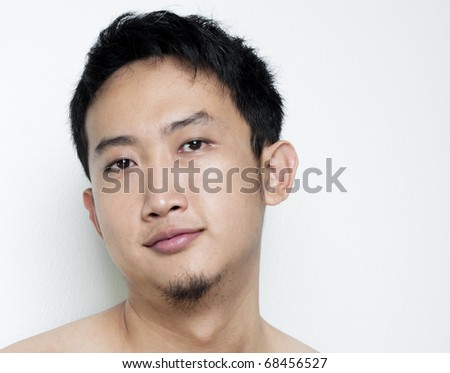 Pan Asian male portrait on plain background