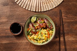 Pan asian style chicken wings in teriyaki sauce with lime, sesame seeds, rice and vegetables in green ceramic bowl over wooden aged background with wooden fan, soy sauce and chopsticks. Top view