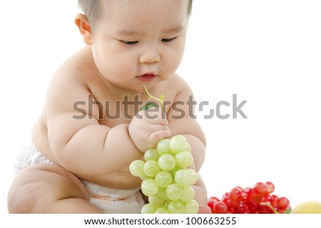Pan Asian Vegetarian baby playing with fruits on white background - stock photo