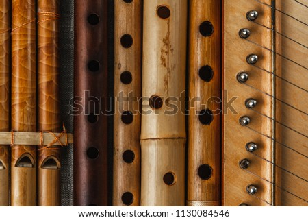 Pan flute and simple wooden flutes next to the psaltery, close-up #1130084546
