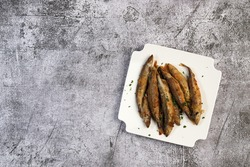 Pan fried capelin or smelt fish on a white square  plate on a dark background. Top view, flat lay