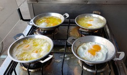 Pan fried egg - Making of four (4) pan fried eggs on a strove at one of a famous local restaurant in province of Loei. Tripical breakfast. To be served with topping, grounded pork and chinese sausage.