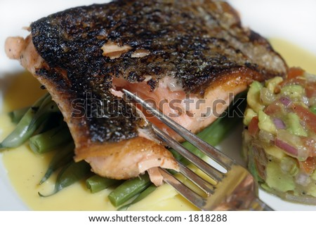pan fried or sauteed salmon fillet on asparagus and lemon butter sauce, served with avocado, tomato and onion salsa. A fork is breaking into the cooked flesh. Macro shot.