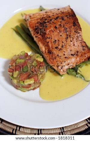 pan fried or sauteed salmon fillet on asparagus and lemon butter sauce, served with avocado, tomato and onion salsa. Flesh side up showing rich red 'grill' effect and pepper.