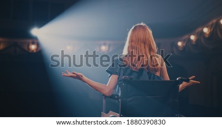 Pan left view of young woman smiling and gesticulating while sitting on wheelchair in spotlight and talking to audience during performance in dark theater