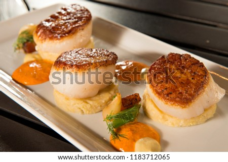 Pan Seared Diver Scallops with Polenta on a white serving dish