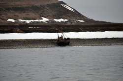 Pan view of abandoned rusty fishing trawler on the  coastline in Barents sea