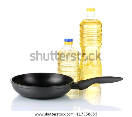 Pan with bottle of oil isolated on white