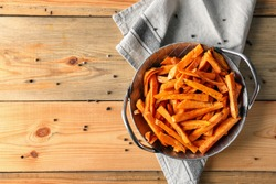 Pan with sweet potato fries on wooden table