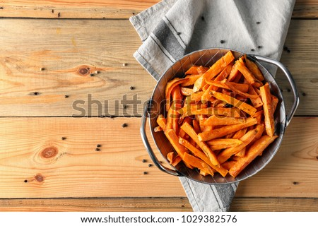 Pan with sweet potato fries on wooden table #1029382576