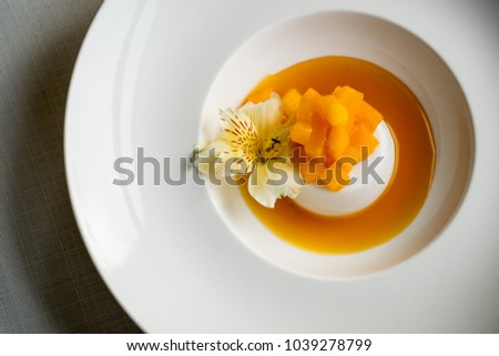 Panacotta dessert with mango and orange fruit in white plate on table background. Flat top view, from above.