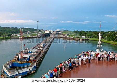 PANAMA CANAL - NOV 7:  Tourists stand on bow of cruise ship as it enters first lock of Panama Canal on November 7, 2009 in Panama Canal. - stock photo