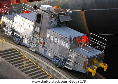 PANAMA - OCTOBER 6. In July 2009, the Panama Canal Authority awarded contracts to a consortium of companies to build six new locks by 2015. Ship towing locomotive at Balboa. October 6, 2010, Panama