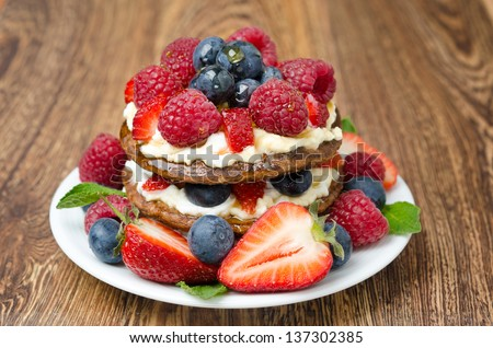 Pancake cake with whipped cream and fresh berries on the wooden table closeup - stock photo