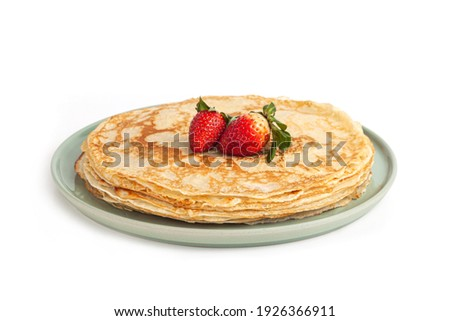 Pancake on green plate on white background. Many pancakes are stacked. Thin pancakes with crispy crust. Maslenitsa. Pancakes for breakfast and carnival. Food background. Stockfoto ©
