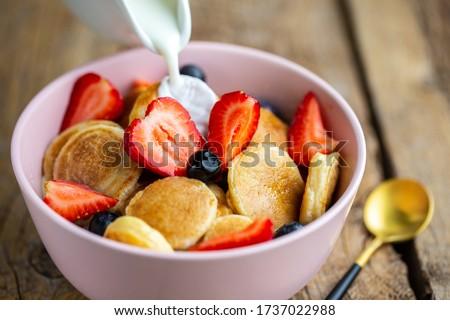 Pancake porridge, mini pancakes in a bowl with milk and maple syrup. Dutch mini pancakes are called strawberry and potato pancakes. Milk is poured onto mini pancakes with strawberries and blueberries.