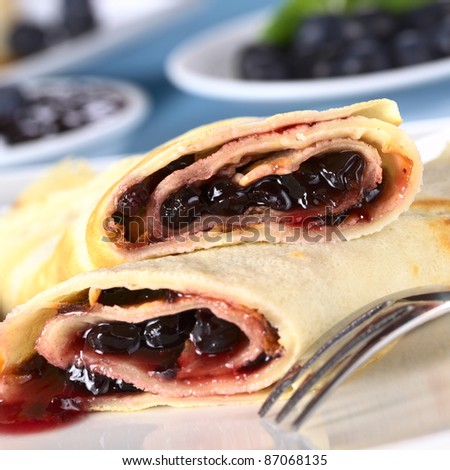 Pancakes filled with blueberry jam with fresh blueberries and jam in the back (Selective Focus, Focus on the front of the upper pancake roll)