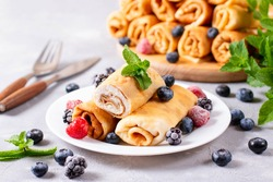 Pancakes filled with cottage cheese and berries. Rolled pancakes
