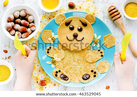 Pancakes for baby breakfast. Bear pancakes with honey and nuts - creative idea for children breakfast or dessert, funny food art for kids, edible picture on a plate top view