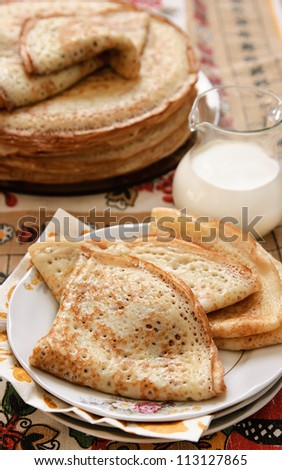 pancakes in a rustic style, three on the plate, milk jug beside, pancakes slide in the background, multicolored textile background