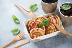 Pancakes in a takeaway carton container with coffee, studio shot on a light-blue stone background, selective focus