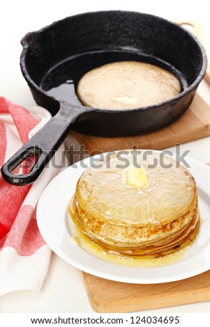 Pancakes on plate and pancake in pan on table