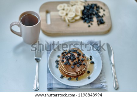 Pancakes poured with honey, syrup and sprinkled with berries. In the background - sliced fruit, a cup of tea, a knife, a fork. #1198848994
