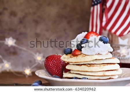 Pancakes served with blueberries, strawberries, and whipped cream against a rustic background. Perfect for fourth of July. Shallow depth of field with selective focus.