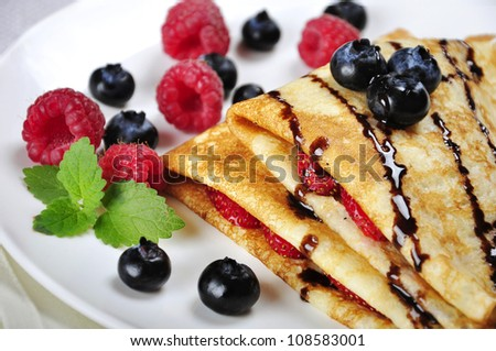 Pancakes served with raspberries, blueberries and chocolate on plate. Shallow dof