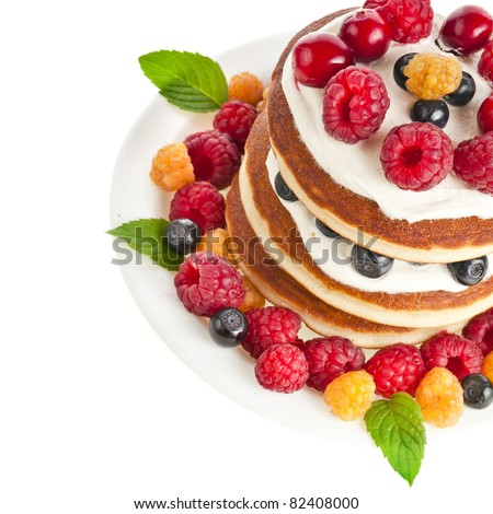 Pancakes stack with fresh forest berries  on white background