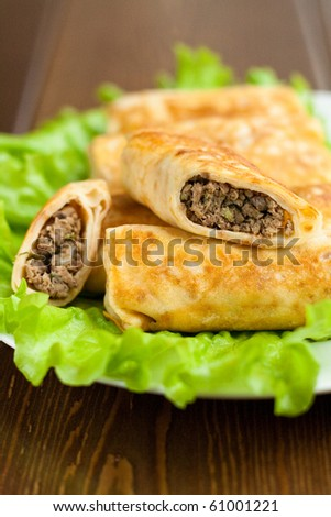 Pancakes stuffed with meat served with lettuce