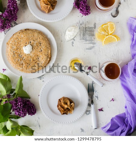 Pancakes, thin stuffed pancakes with sour cream. With lilac decor. On a white stone table. #1299478795