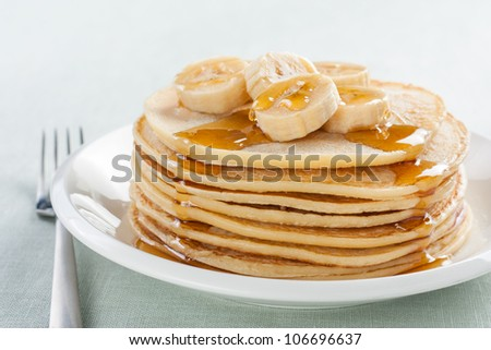 pancakes with banana and syrup on white plate