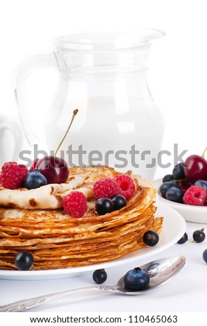 Pancakes with berries and jug of milk