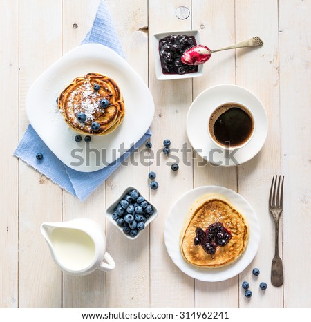 pancakes with blueberry and coffee on wooden background. top view #314962241