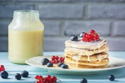 Pancakes with condensed milk and berries. Tasty breakfast with blueberries and currants. Delicious healthy food. Photo of a fresh natural dessert.