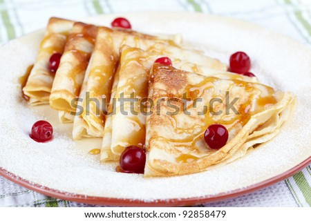 Pancakes with cranberry berries and honey on a white plate
