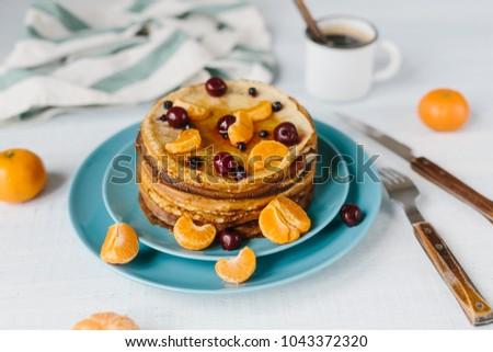 Pancakes with honey, cherries, wild berries and tangerines